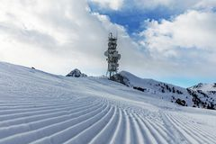 A transmitter at the top of a mountain in the Dolomites ski area. Empty ski slope in winter on a sunny day. Prepare ski slope, Alp Stock Images