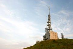 Transmitting station. In a peak under blue sky Royalty Free Stock Image