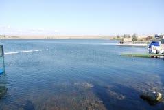 Transparant duidelijk water van een blauw meer met pijlers langs de kust stock foto's