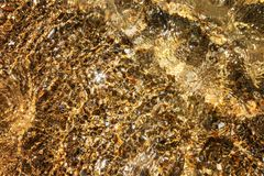 Transparant zeewater met zonhoogtepunten en zandige bodem stock foto