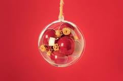 Transparante bal met rode Kerstmisballen binnen op rode backgr Stock Afbeeldingen