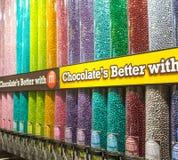 Transparante die buizen met M&M-suikergoed door Mars worden gevuld Stock Foto's