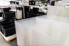 Transparante en zwarte plastic containersstapel in een opslag stock foto