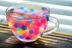 Transparante kop dichte omhooggaand Kleuren van regenboog Multicolored hydrogelballen Kleine kleurrijke parels De woordkleur op g royalty-vrije stock foto's