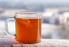 Transparante kop met hete kruidige drank, citroen en sinaasappel op de achtergrond van de de winterstad Stock Afbeeldingen