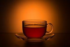 Transparante kop thee op een achtergrond van oranje vlekken Royalty-vrije Stock Afbeeldingen