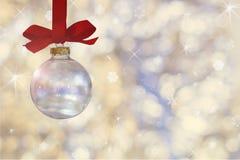 Transparante lege Kerstmisbal De Kerstmissnuisterij, hangt op een rood lint op achtergrond van defocused zilveren lichten royalty-vrije stock fotografie