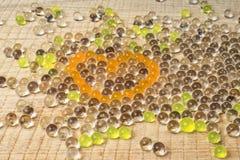 Transparante parels in de vorm van een hart op een bord Stock Fotografie