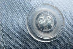 Transparante ronde die knoop aan blauwe doek wordt genaaid Stock Foto