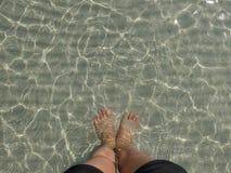 Transparante waterrimpeling, zandgolven en zonlichtglans zeebodem met mensenbeen en voettribune Royalty-vrije Stock Foto's