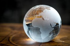 Transparency global, world or international concept with decoration glass globe on vintage book with dark background.  stock images