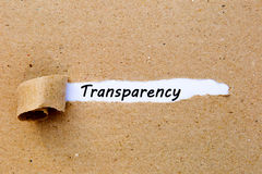 Transparency - printed text underneath torn brown paper stock photography