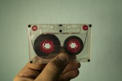 Audio cassette in hand. Transparent audio cassette in hand on a blue background stock photos
