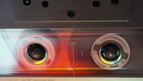 Transparent audio cassette. Horizontal tracking footage of transparent audio cassette playing stock video