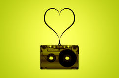 Transparent Audio Cassette Tape with Heart Made of Tape. An image of a transparent cassette tape on a lime green and yellow background with a strip of tape stock image