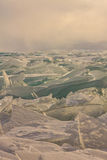 Transparent Baikal ice hummocks at sunset in the fog.  Royalty Free Stock Photography