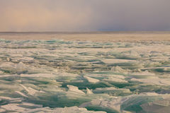 Transparent Baikal ice hummocks at sunset in the fog Stock Photo