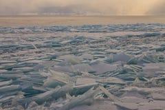 Transparent Baikal ice hummocks at sunset in the fog.  Stock Photos