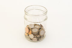 Transparent bank with coins. Of different metals of different denominations from different countries Stock Photos