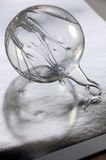 Transparent bauble on silver paper Royalty Free Stock Photography