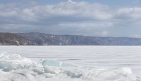 Transparent blue ice hummocks on lake Baikal shore. Siberia winter landscape view. Snow-covered ice of the lake. Big