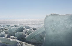 Transparent blue ice hummocks on lake Baikal shore. Siberia winter landscape view. Snow-covered ice of the lake. Big Royalty Free Stock Photography