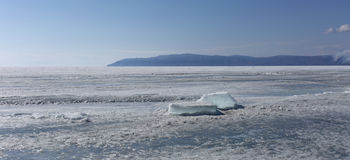 Transparent blue ice hummocks on lake Baikal shore. Siberia winter landscape view. Snow-covered ice of the lake. Big Stock Photography