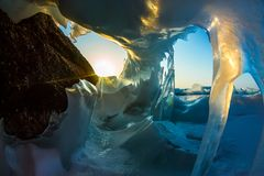 Transparent blue icicle ice cave in Lake Baikal.  royalty free stock images