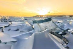 Transparent blue Toros Baikal ice is shining through the crack sunset