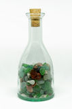 Transparent bottle with colorful stones Royalty Free Stock Photography