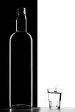 Transparent bottle and Glass. On black and white background Stock Photography