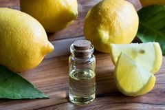 A transparent bottle of lemon essential oil with lemons in the b Royalty Free Stock Photography