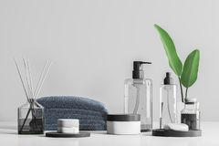 Spa products and creams on table over gray. Transparent bottles with soap and spa products in white mock up containers. Aroma sticks and stack of gray towels on royalty free stock images