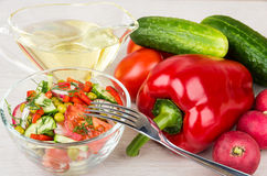 Transparent bowl with vegetable salad, jug vegetable oil and for Stock Photo