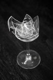 Transparent broken stoup on a darkly grey background. great number of fragments of glass. Great number of fragments of tall wine glass for wine Stock Image