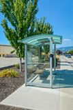 Transparent bus stop station at roadside on sunny day in British Columbia. Urban bus stop shelter at roadside. Transparent bus stop station on summertime in royalty free stock image