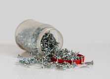 Transparent can with a red lid and scattered screws Royalty Free Stock Image