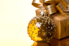 Transparent Christmas ball and gift box on a golden background Royalty Free Stock Photo
