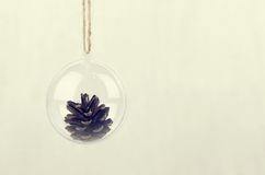 Transparent Christmas ball with a pine cone inside Stock Photo