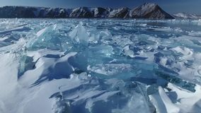 Transparent clean ice floes unique cracks. High mountains. Scenic best popular tourist attraction. North blue frozen water snow. Lake Baikal Russia Buryatia stock footage