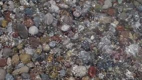 Round pebbles on the beach and a transparent wave. Transparent clean wave on the sea carrying small stones and pebbles along the seashore stock video