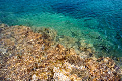Transparent clear water and stones with sunlight reflection Stock Photos