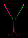Transparent colored empty martini glass on black Stock Photography