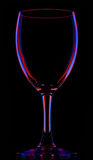Transparent colored empty wine glass on black Stock Images