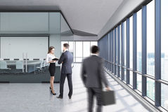 Transparent conference room concrete, side people. People near a meeting room with white and glass walls, concrete floor and a row of folders standing on a shelf Stock Image