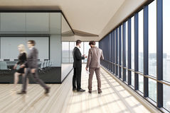 Transparent conference room wood, people. Poeple near a meeting room interior with glass walls, wooden floor and a row of folders standing on a shelf. Square Stock Photos