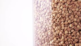 Transparent container with buckwheat. Transparent flask with buckwheat rotates against a white background stock footage