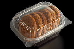 Transparent Container with Oat Cookies. Over black background Stock Photos