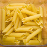 Transparent container with uncooked spaghetti on wooden table Stock Photo