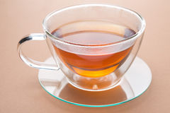 Transparent cup of black tea on a brown background. Close-up Stock Images